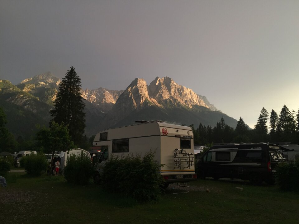Our camper in dramatic light in front of a mountain range.