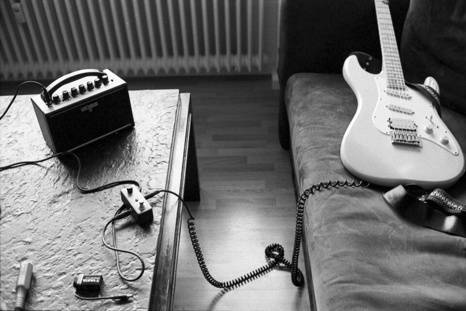 My strat-like guitar on a sofa, connected per cable to the mini looper pedal and the Boss Katana Mini amplifier.